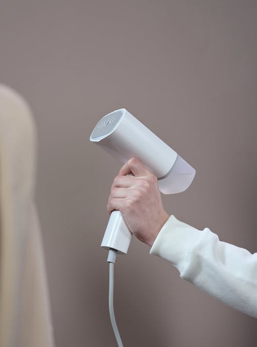Person Holding White and Gray Microphone