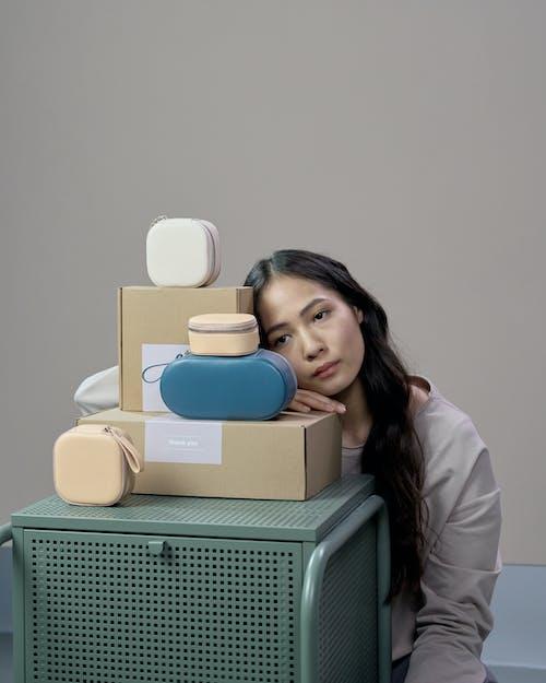 Woman in White Long Sleeve Shirt Holding Blue and White Ceramic Mug