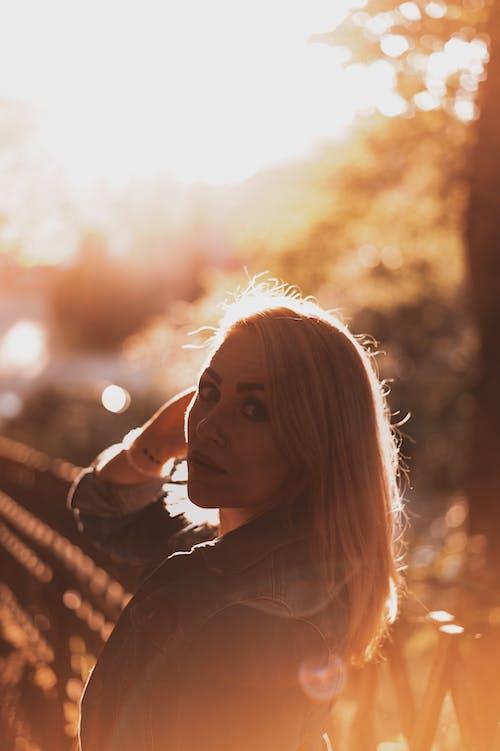 Foto profissional grátis de loira, luz de fundo, pôr do sol