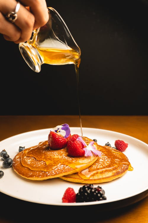 Hand Pouring Honey On Pancakes