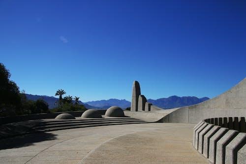 Gratis stockfoto met architectuur, beton, blauwe lucht, bomen