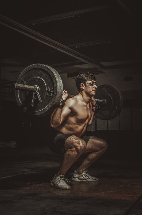 Topless Man in Black Shorts Holding Barbell