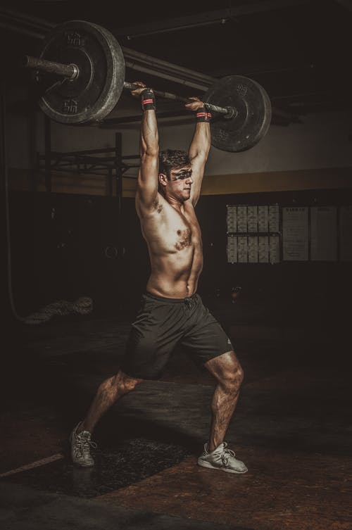 Topless Man Holding Black Barbell