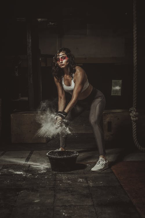 Woman in Black Tank Top and Black Pants Sitting on Floor With White Smoke