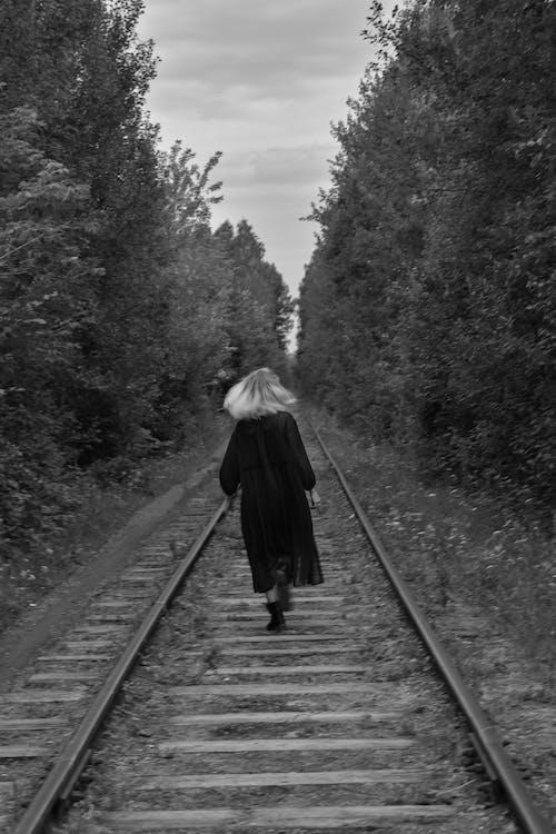 Woman walking on railway in forest