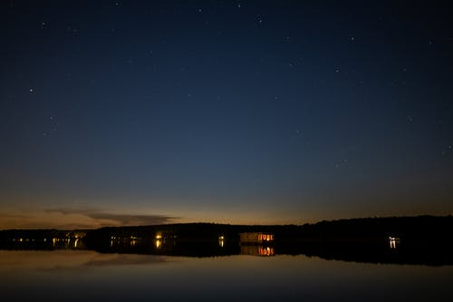 Silhouette of Building Near Body of Water during Night Time