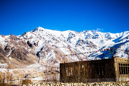 Stone Building at the Base of Snow-covered Mountain Range Under Clear Bright Blue Sky