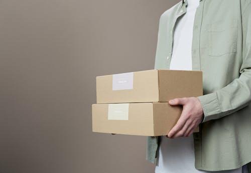 Woman in White Blazer Holding Brown Cardboard Box