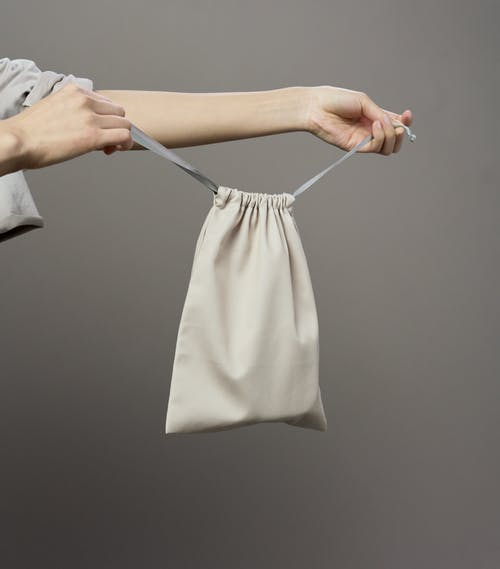 Person Holding White Textile on Clothes Hanger