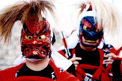 Person's Wearing Red and Blue Kabuki Masks