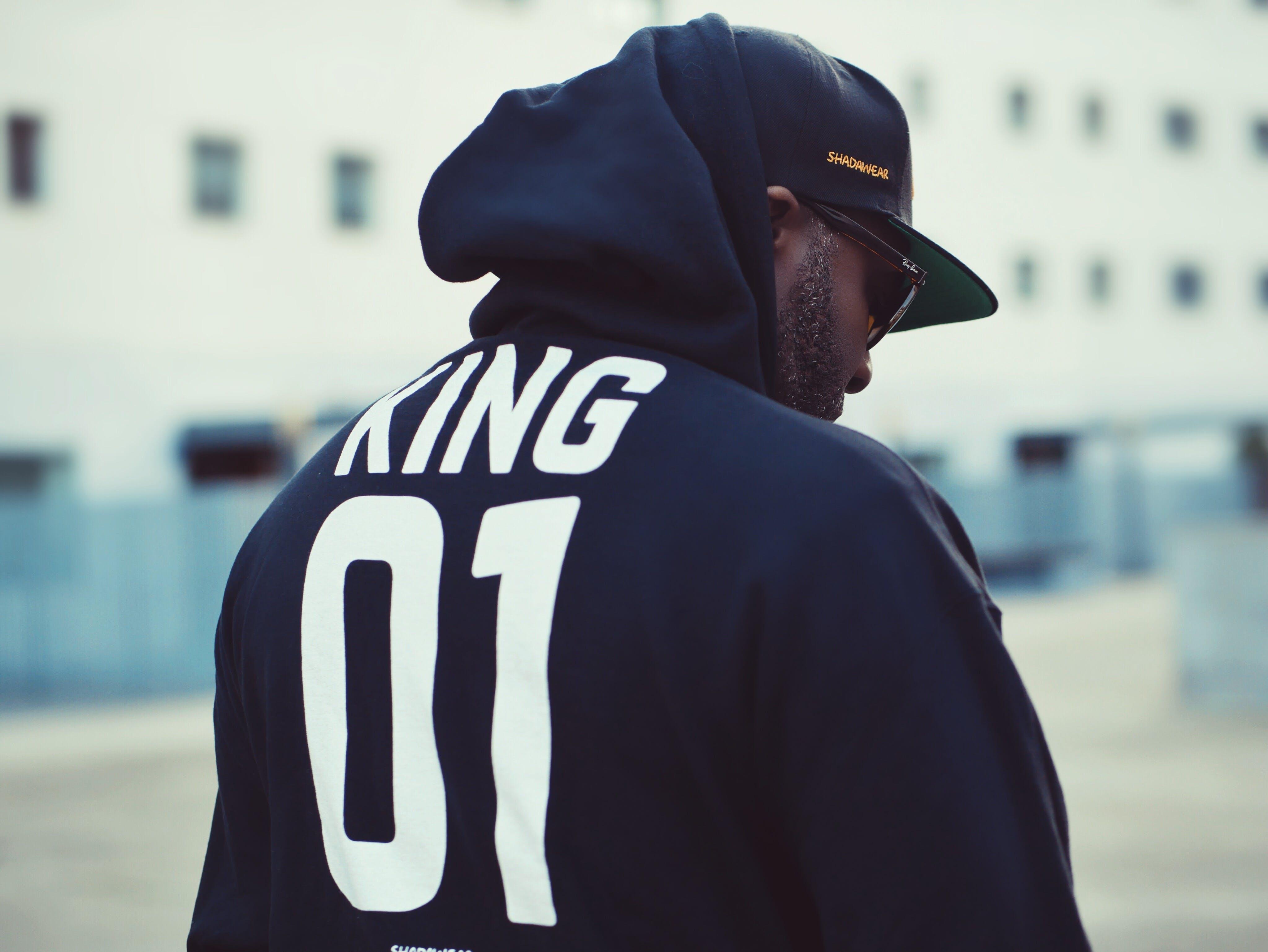 Man Wearing Black King 01-printed Hoodie and Flat Brim Cap