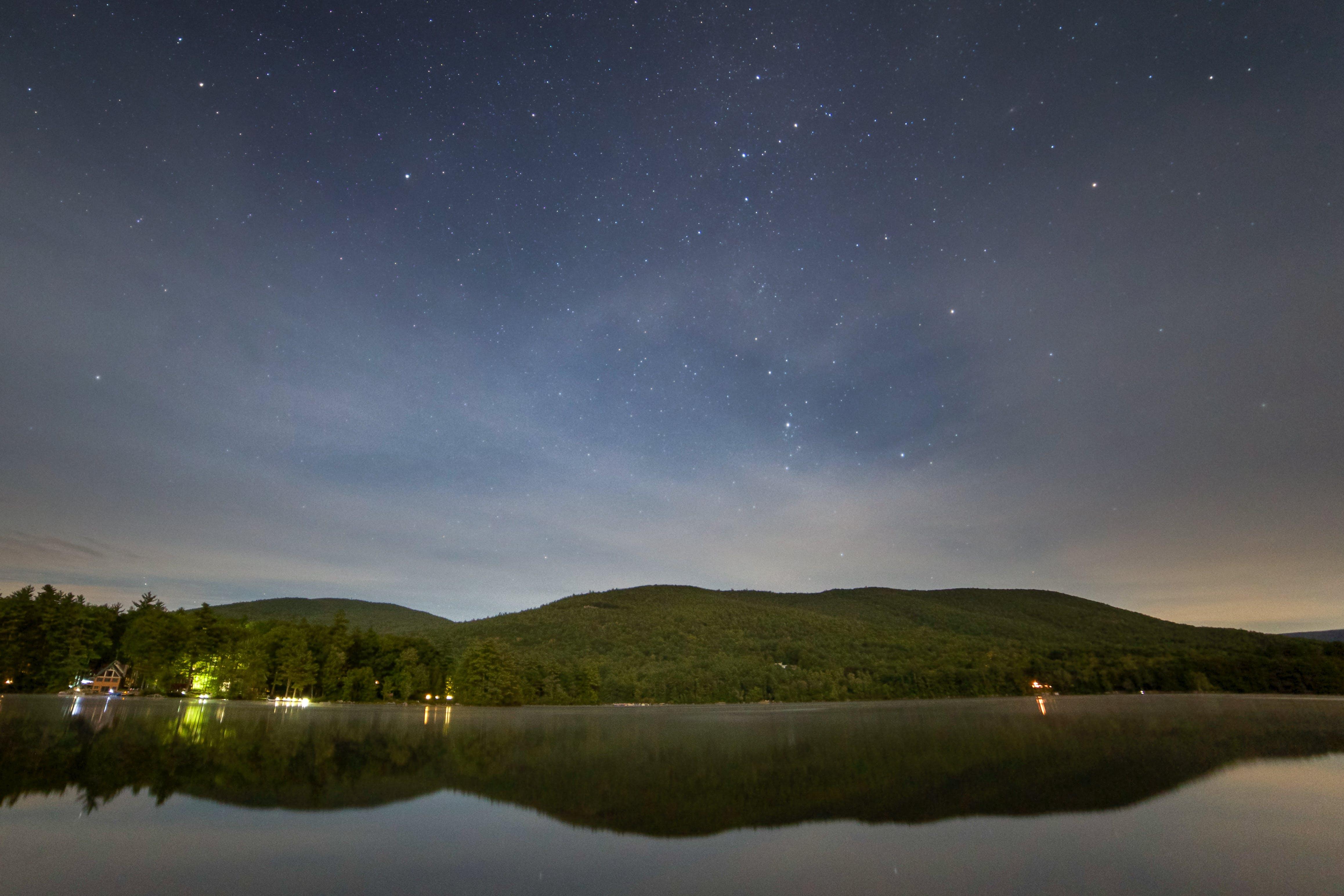 Green Mountain Near Body of Water at Night