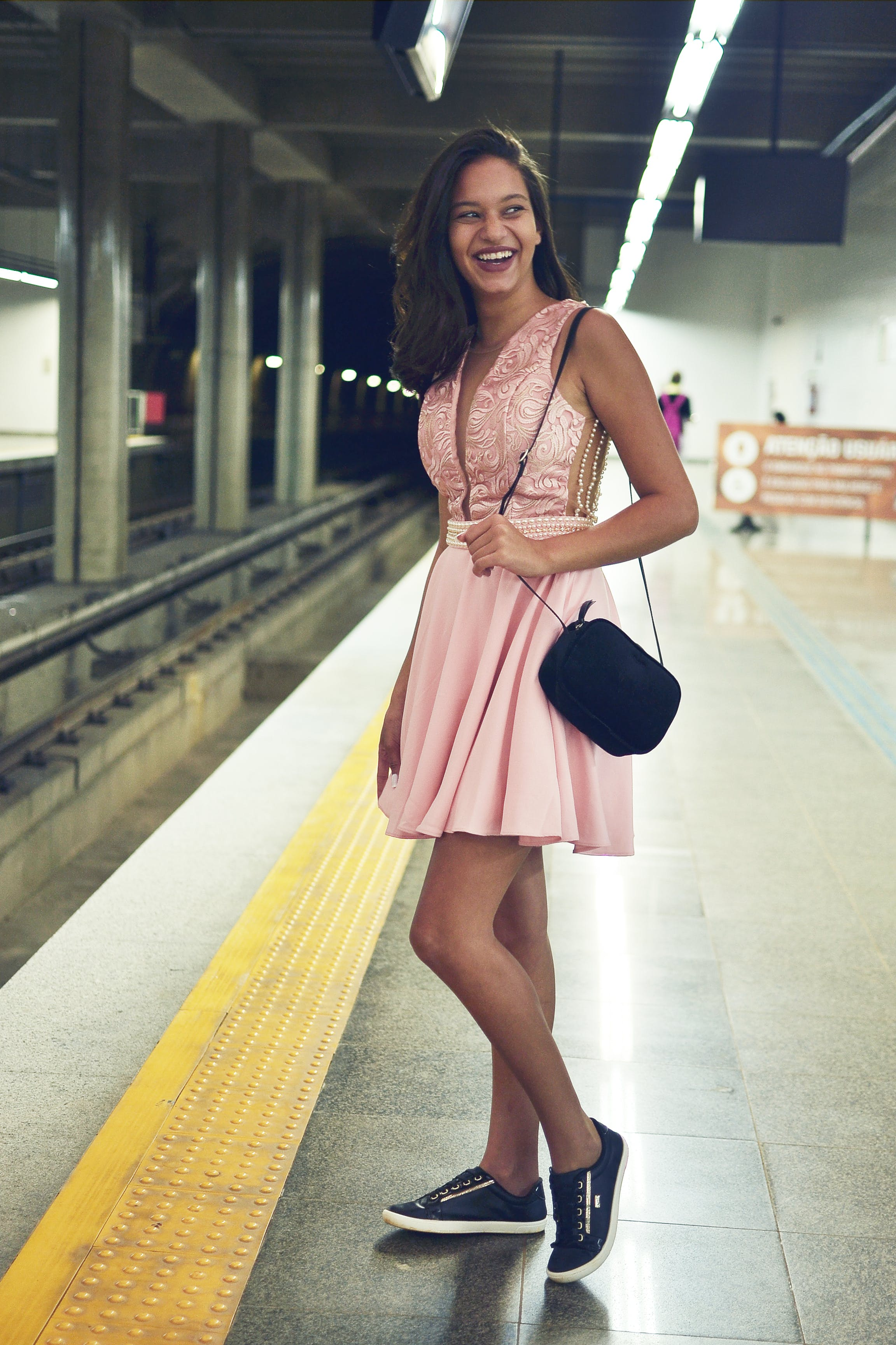 Woman Wearing Pink Plunging Necklace Midi Dress Standing on Train Station