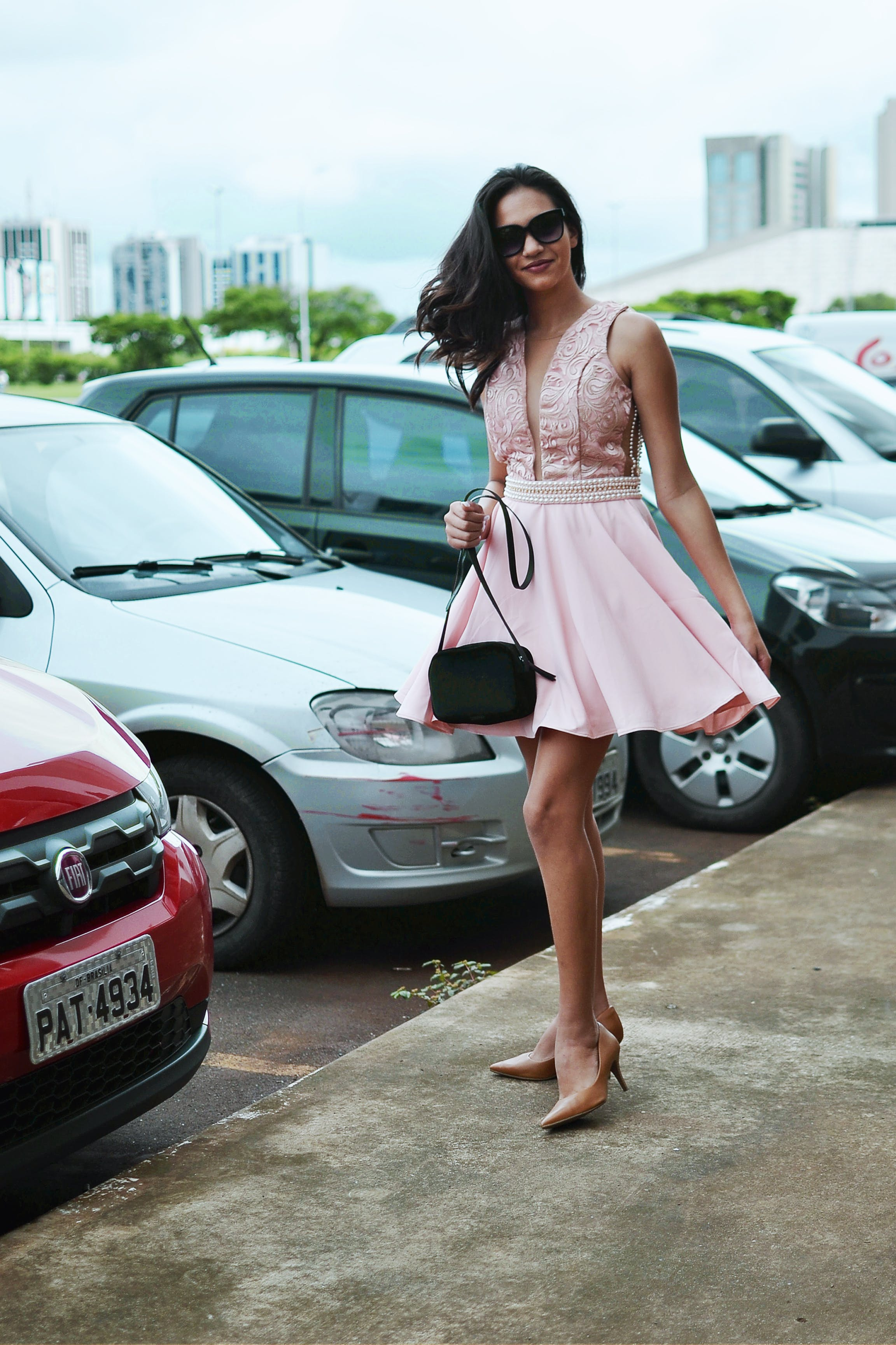 Woman Wearing Pink Sleeveless Dress Holding Black Bag