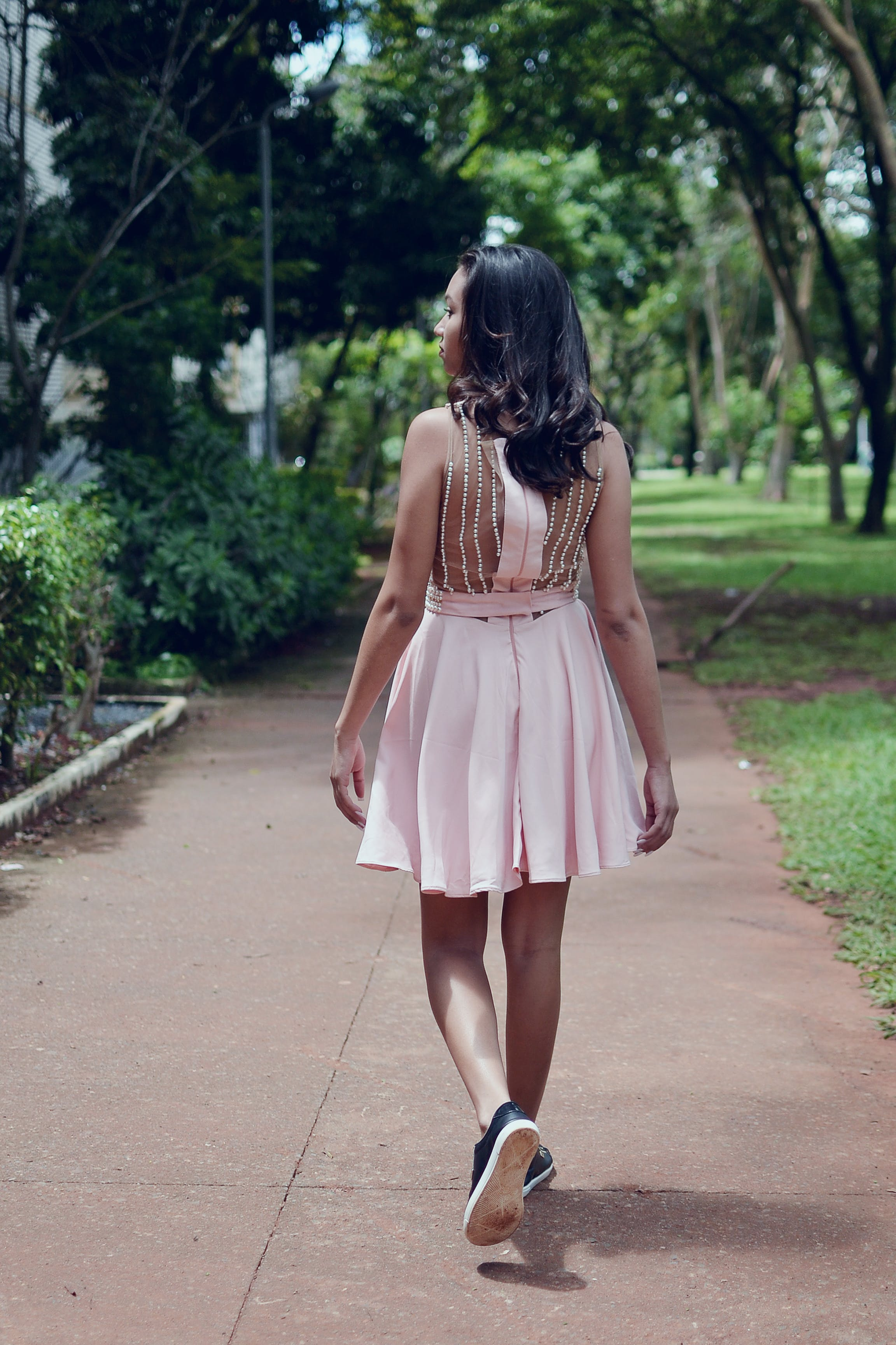 Woman Wearing Pink Mini Dress Walking on Walkway
