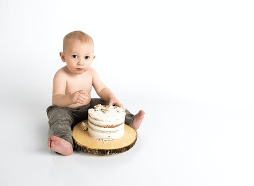 Toddler Sitting Near White Cake