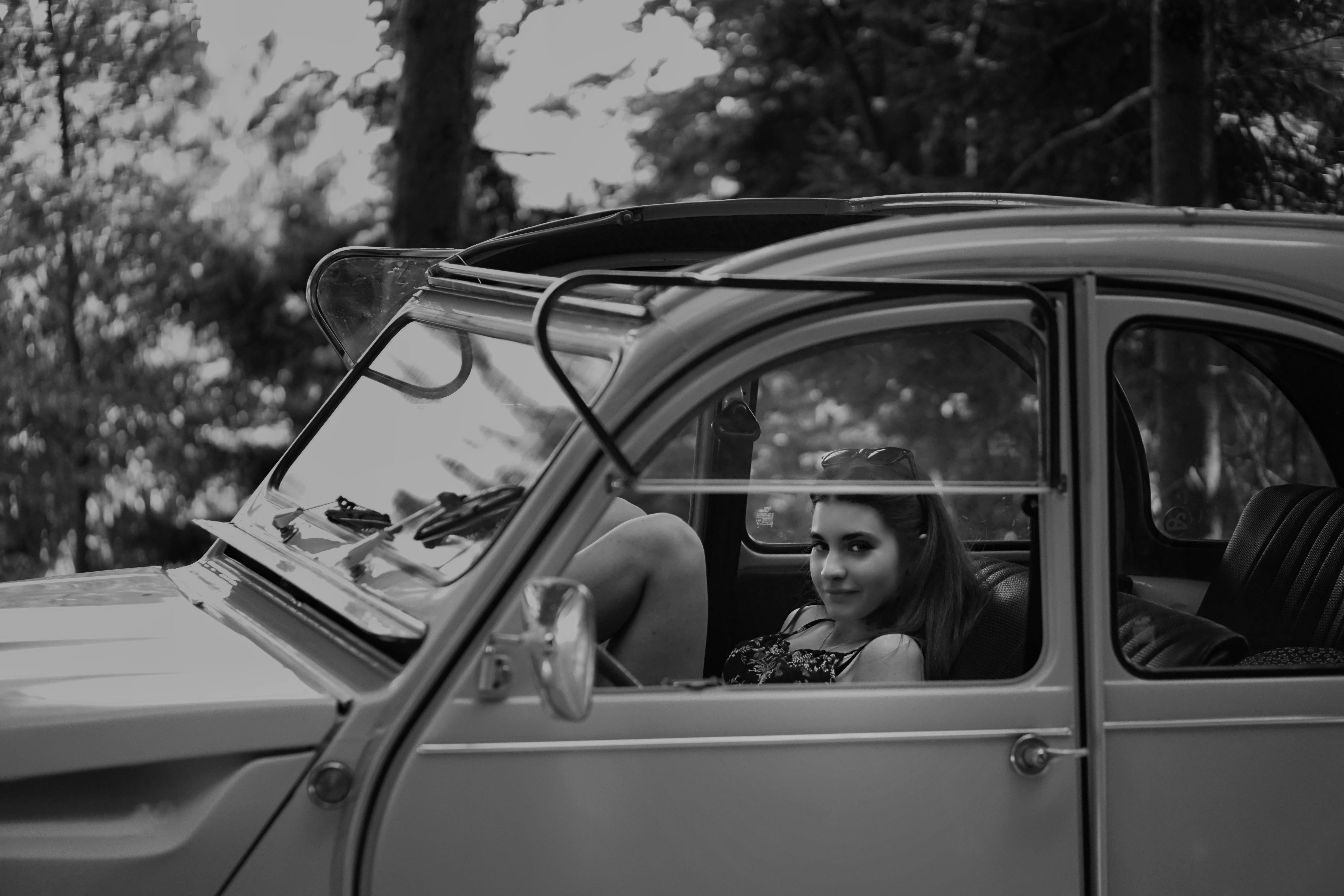 Grayscale Photo Of Woman Inside Classic Car