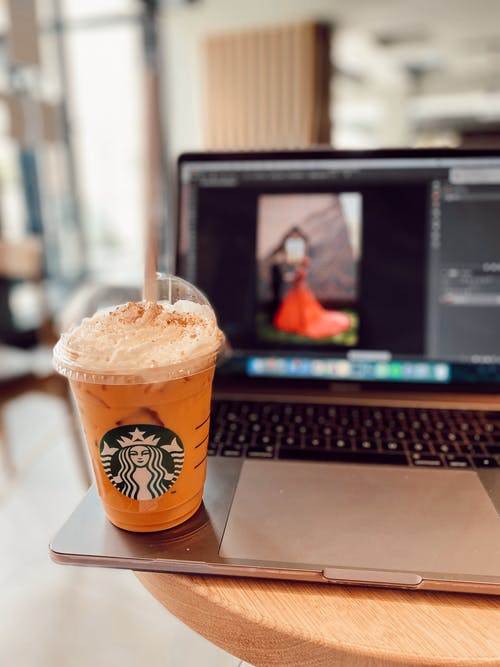 Orange and White Disposable Cup on Macbook Pro