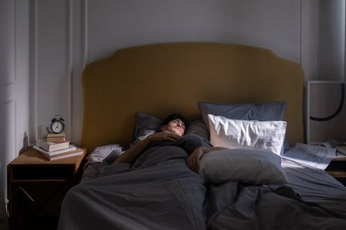 Man in Gray T-shirt Lying on Bed