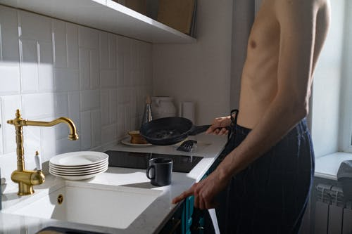 Topless Man Standing in Front of Sink