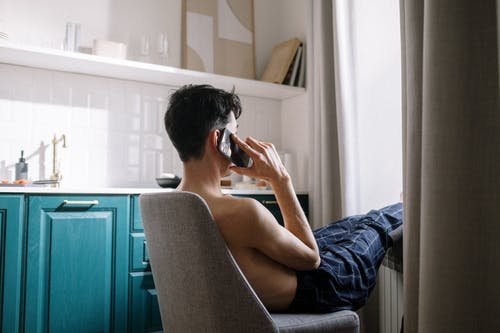 Side view of man sitting on chair and talking on phone