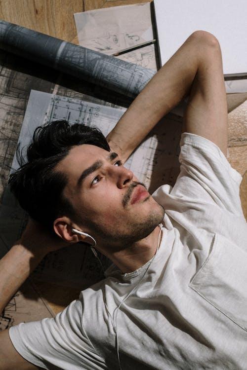 Man in White Polo Shirt Lying on Floor