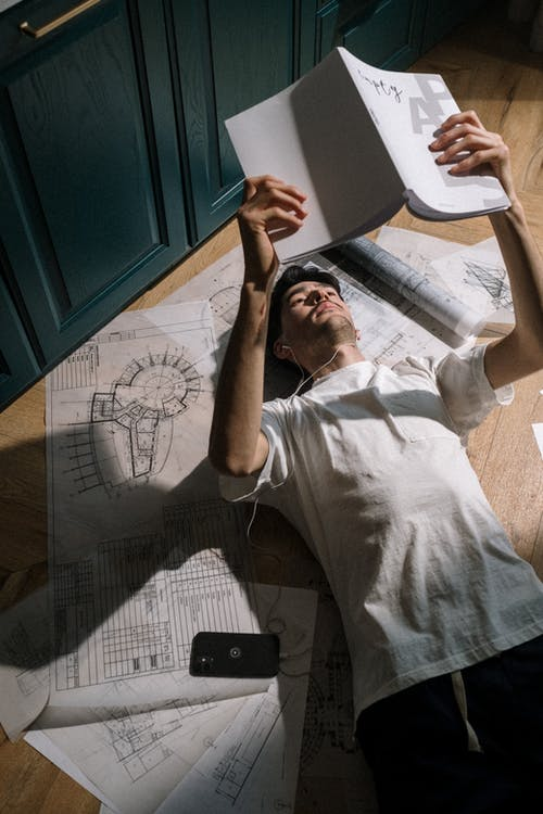 Adult man laying down on floor among drawings and reading book