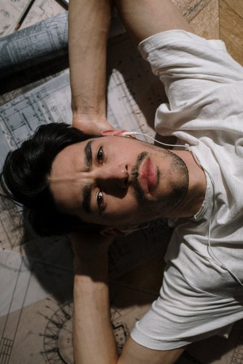 Adult man laying down among drawing with hands behind head