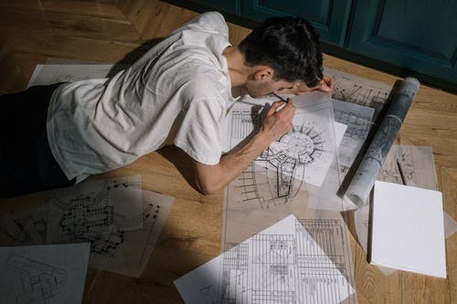 Adult man laying down on floor and drawing