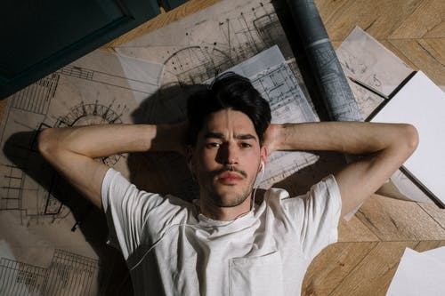 Adult man laying on floor among drawings with hands behind head