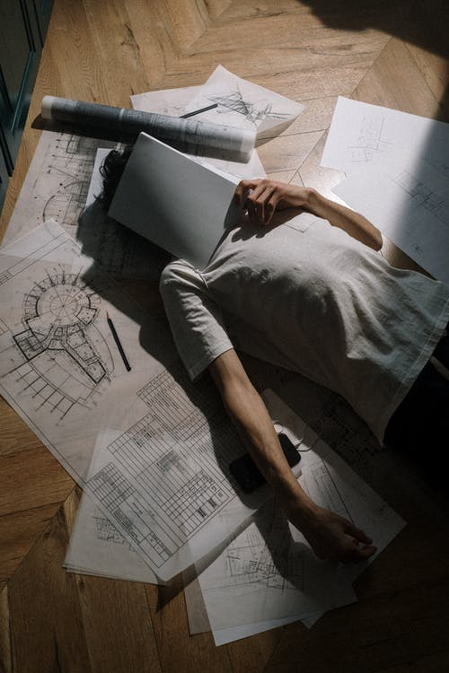 Adult man laying down on floor with book on head