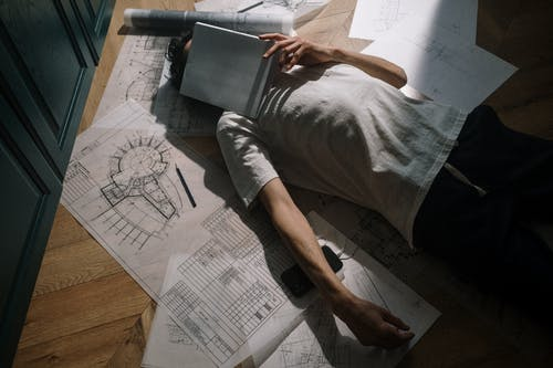 Man laying down on floor with notebook on face