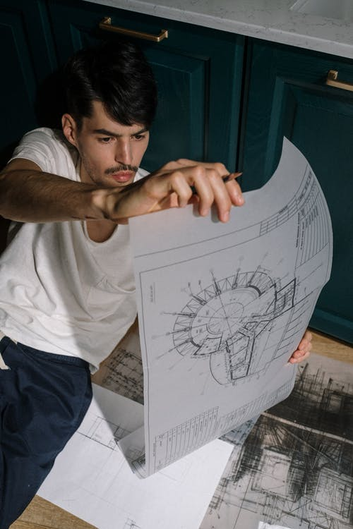 Adult man sitting on floor and looking at drawing