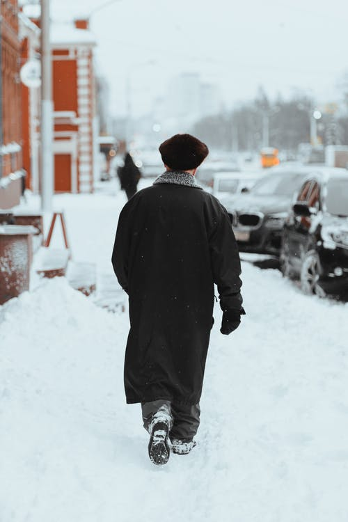 Man in Black Coat Walking on Snow Covered Road