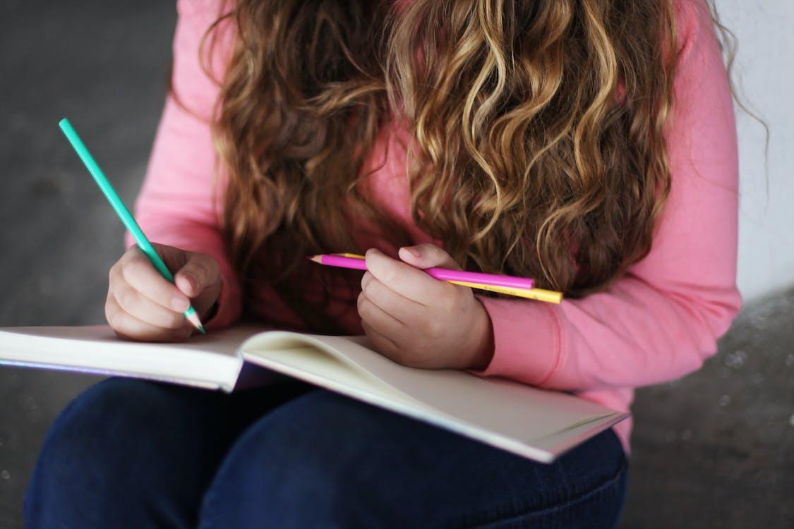 Crop woman drawing in sketchbook