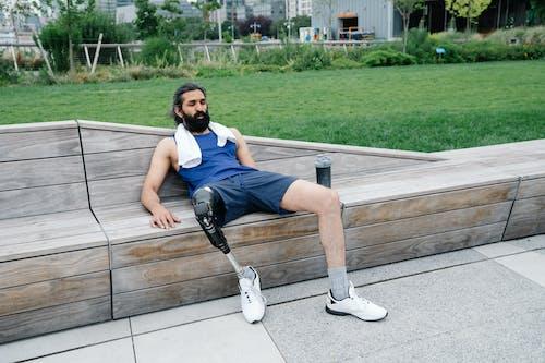 Foto profissional grátis de adulto, ao ar livre, banco de madeira