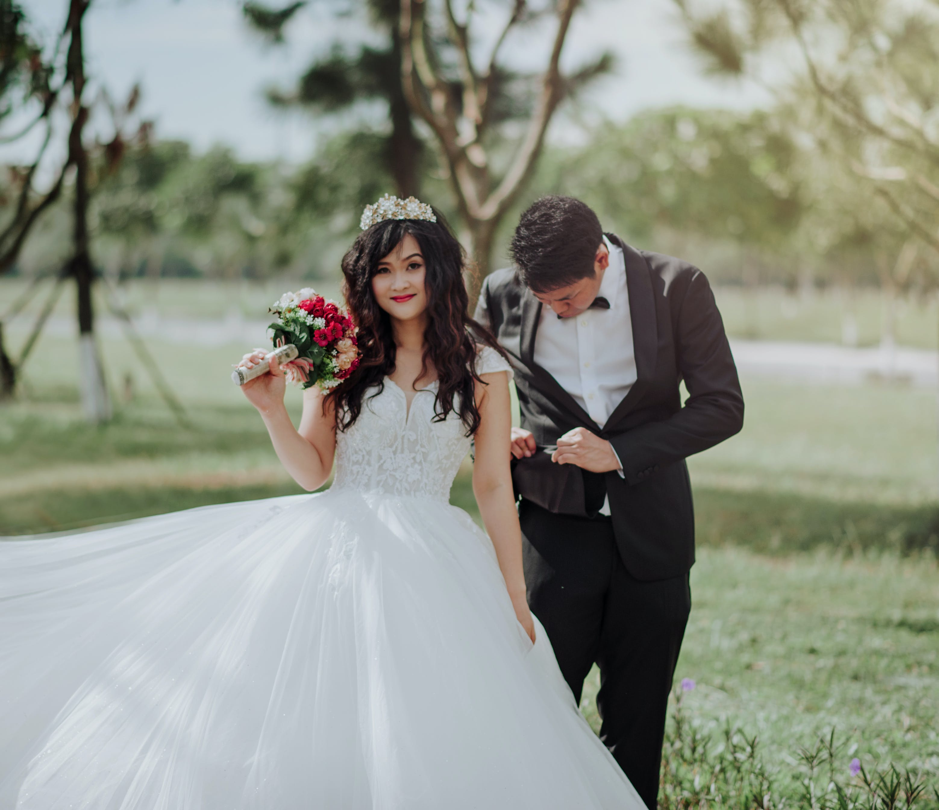 Woman in Wedding Dress Holding Flower With Man in Black Blazer