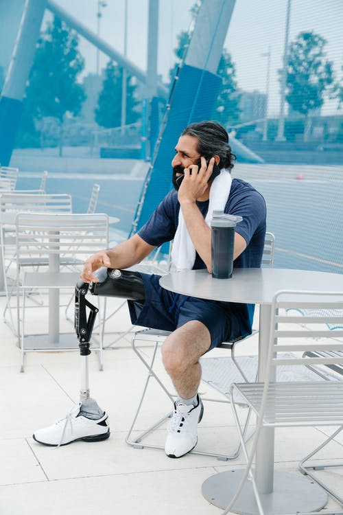 Sitting man with prosthetic leg talking on phone