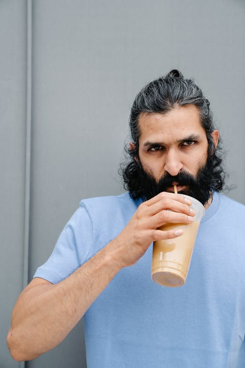 Close-up Photo of Man drinking Iced Coffee