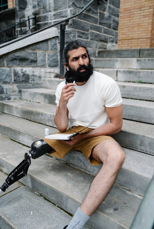 Man with prosthetic leg sitting on stairs