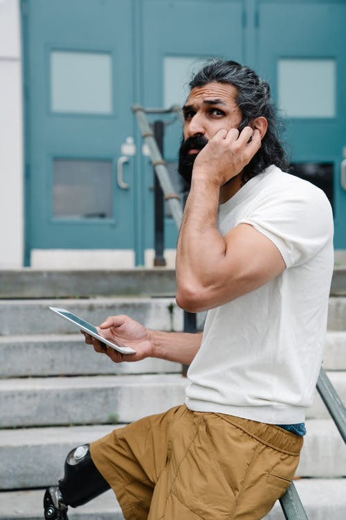 Man with prosthetic leg leaning on railing using phone