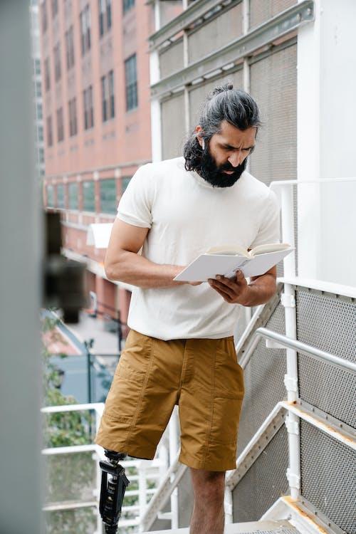 Standing man withprosthetic leg reading book