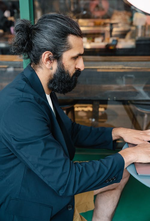 Hipster with earring sitting at table and typing on laptop at shop window
