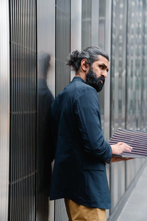 Standing man holding laptop