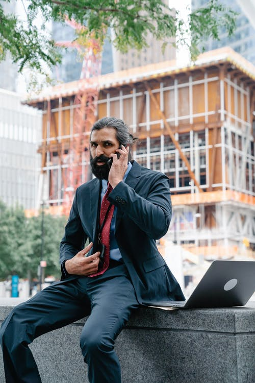 Man talking on phone with construction work in background