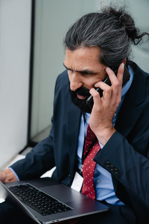 Man using laptop while talking on the phone