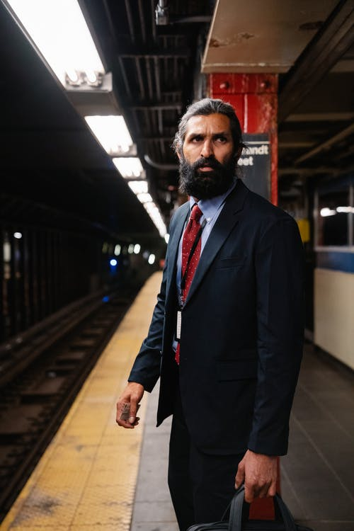 Man i a suit awaiting the subway