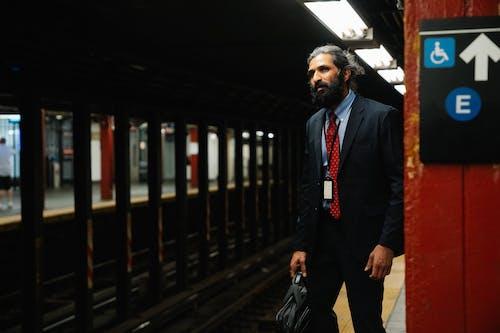地下鉄のプラットホームに立っているスーツの男
