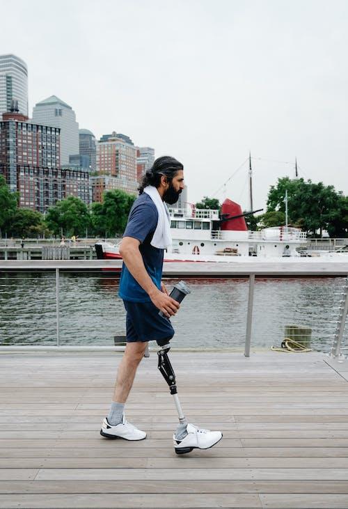 Спортсмен с протезом ноги идет по деревянной тропе