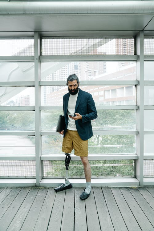 Man with prostheticleg looking at his phone, holding laptop